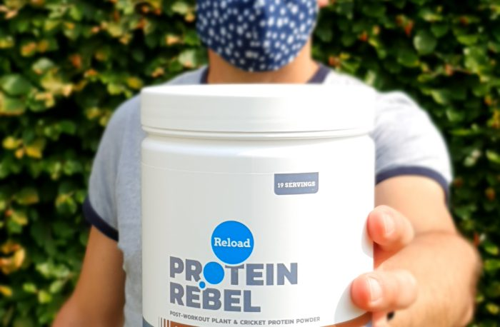 A man with PPE holding a tub of Protein Rebel